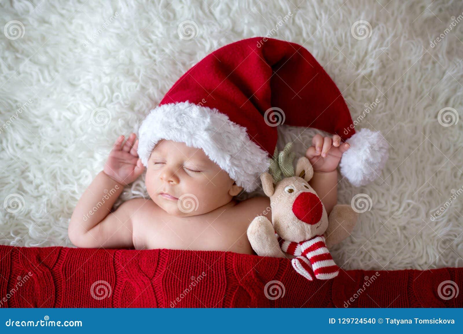 小睡觉的新出生的男婴,佩带的圣诞老人帽子