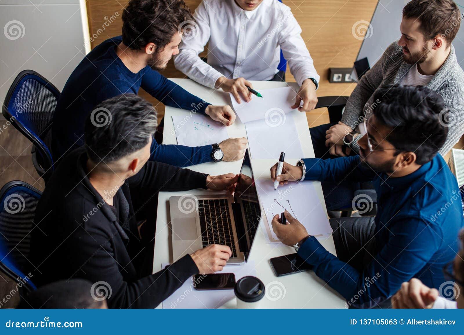 小组商人在现代会议室谈论工作结果