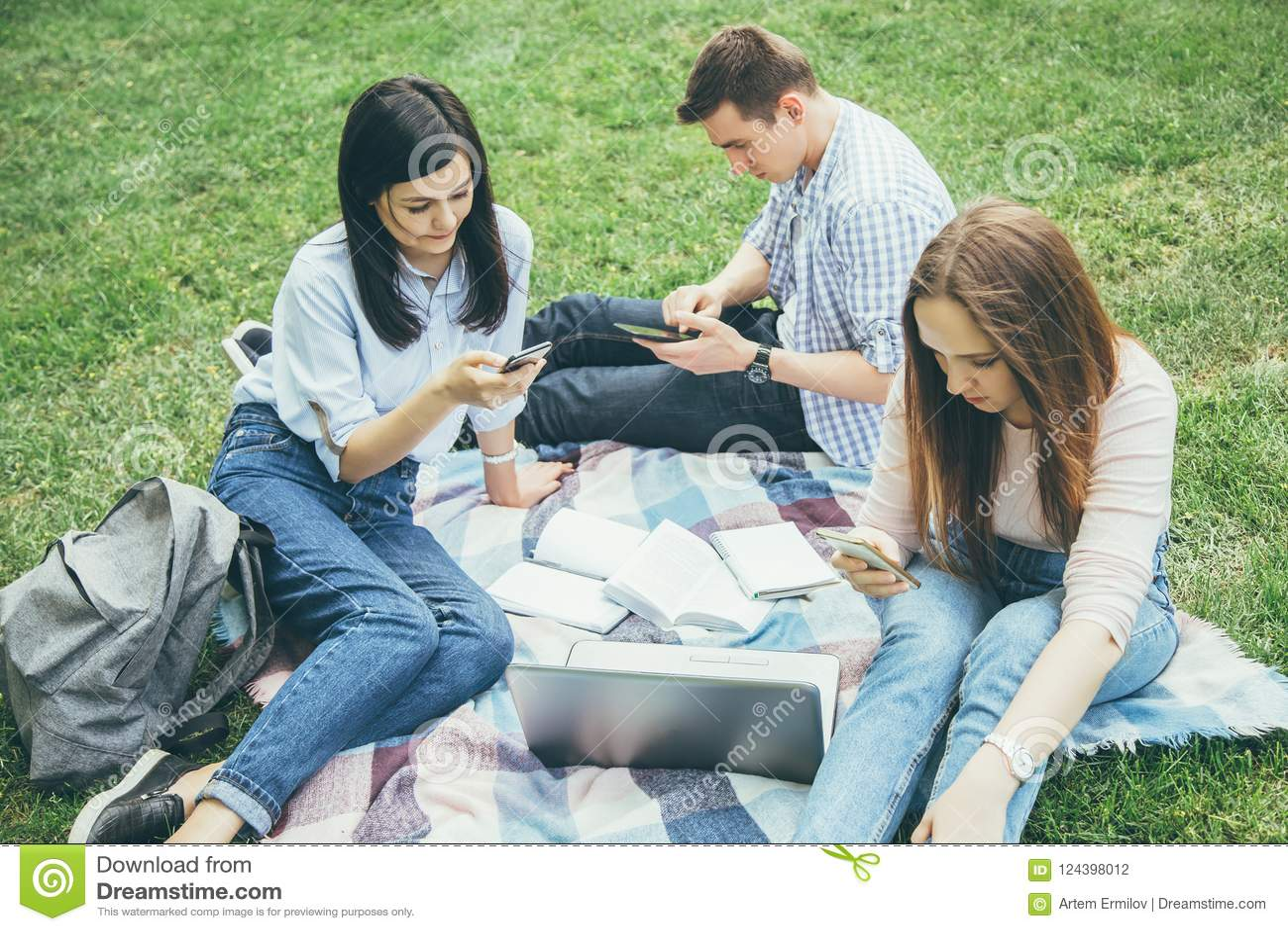 小组坐户外使用手机的大学生