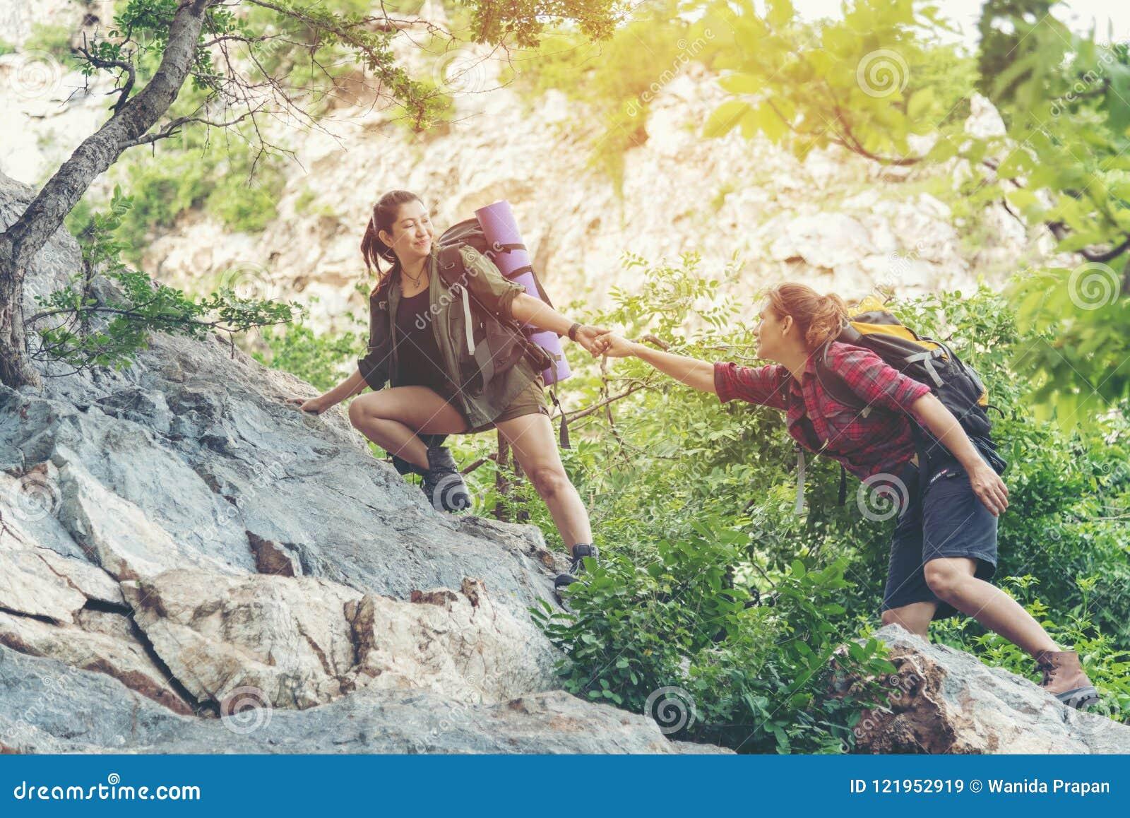 小组帮助她的朋友的远足者妇女爬上日落的最后部分在山的 走在室外lifest的旅客配合