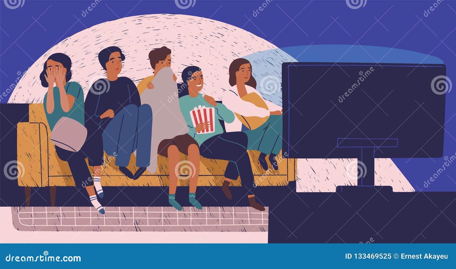 小组朋友坐沙发或长沙发在黑暗和观看的可怕电影中 少女和男孩有害怕的面孔的