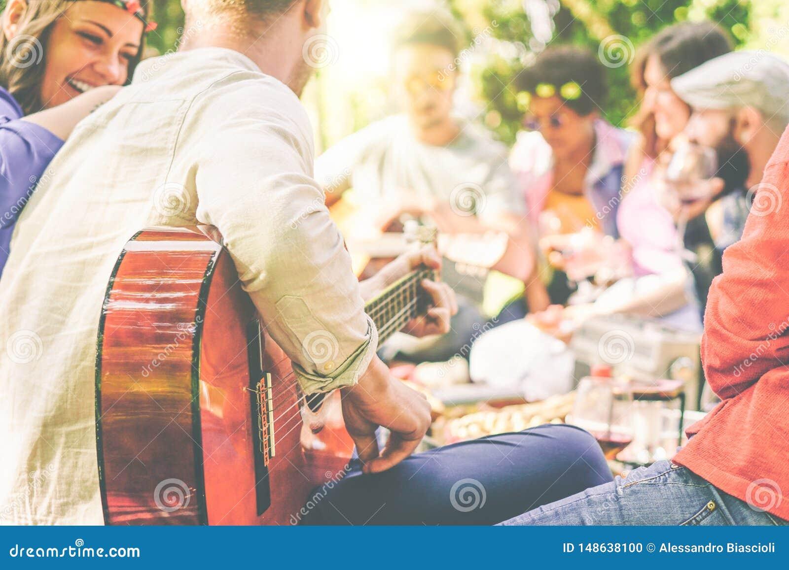 小组朋友有野餐在室外的公园-享受野餐的愉快的年轻伙伴演奏吉他,唱歌的和饮用的酒
