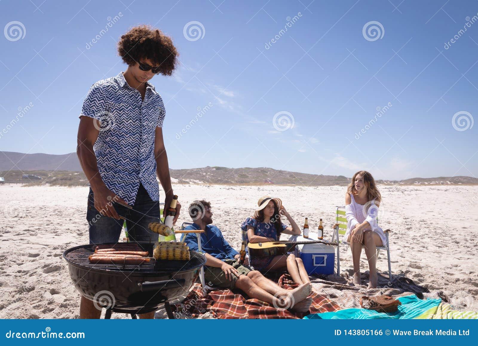 小组朋友获得乐趣在海滩在阳光