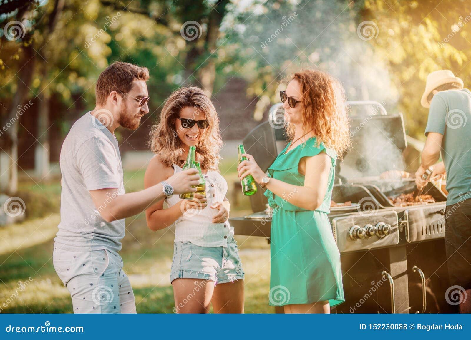 小组朋友获得乐趣在烤肉聚会,喝和微笑和烹调