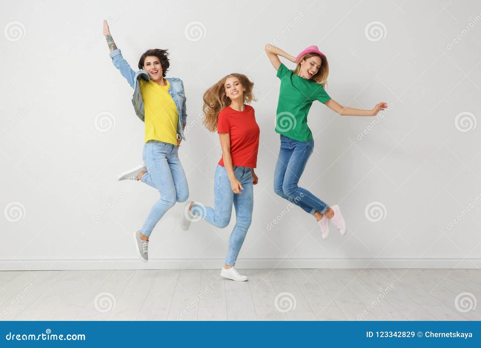 小组牛仔裤和五颜六色的T恤杉的少妇