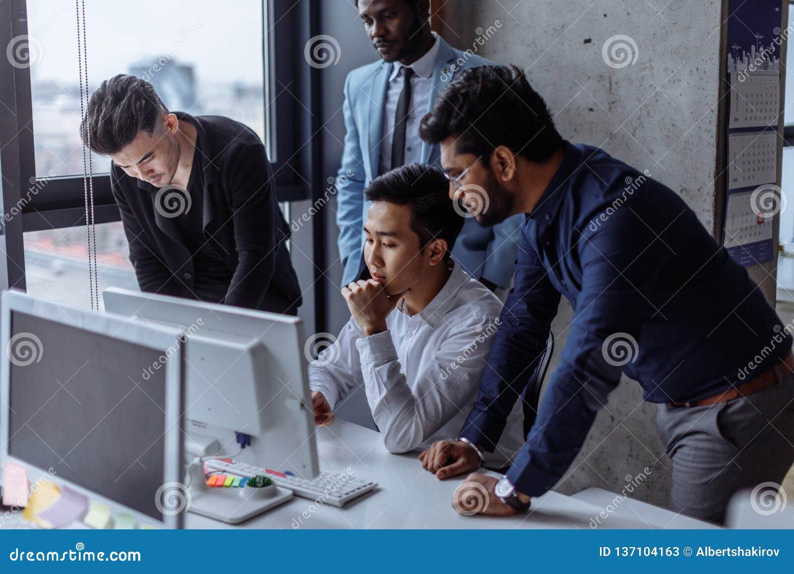 小组聚焦了在办公室谈话的计算机附近被会集的男性商人