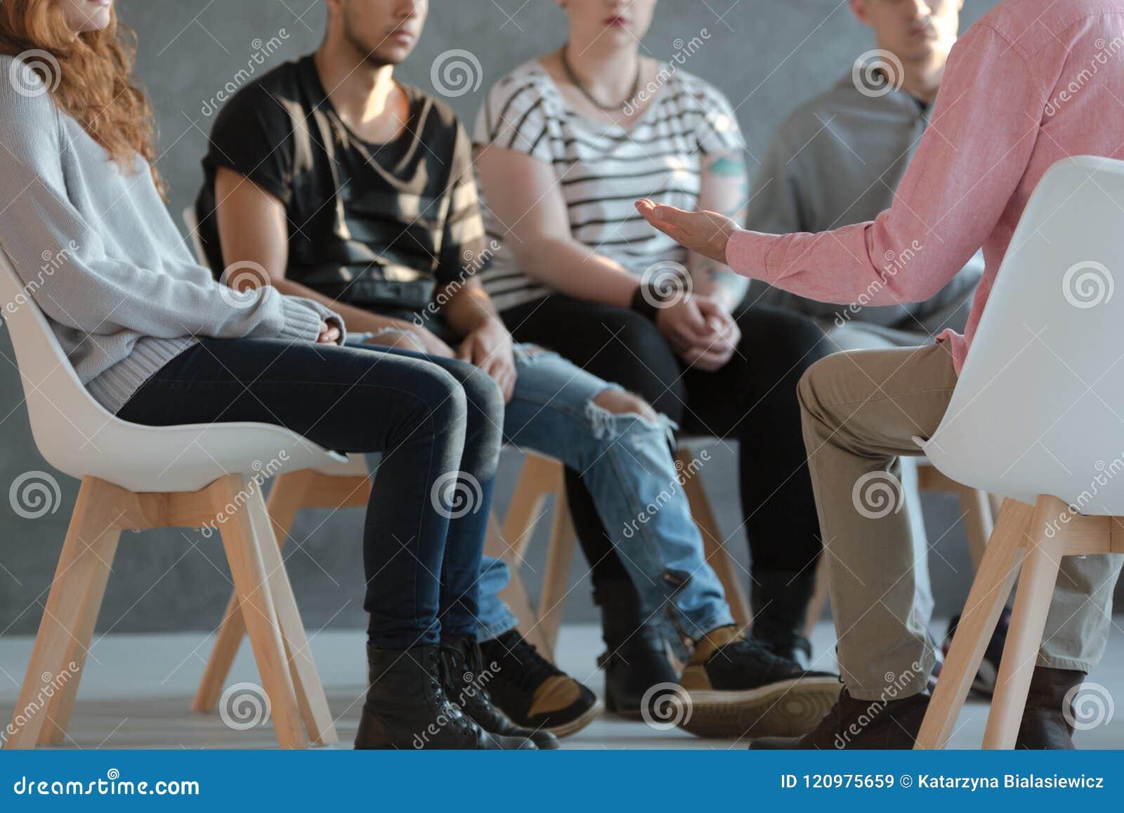 小组青年人坐在圈子和谈话与psych
