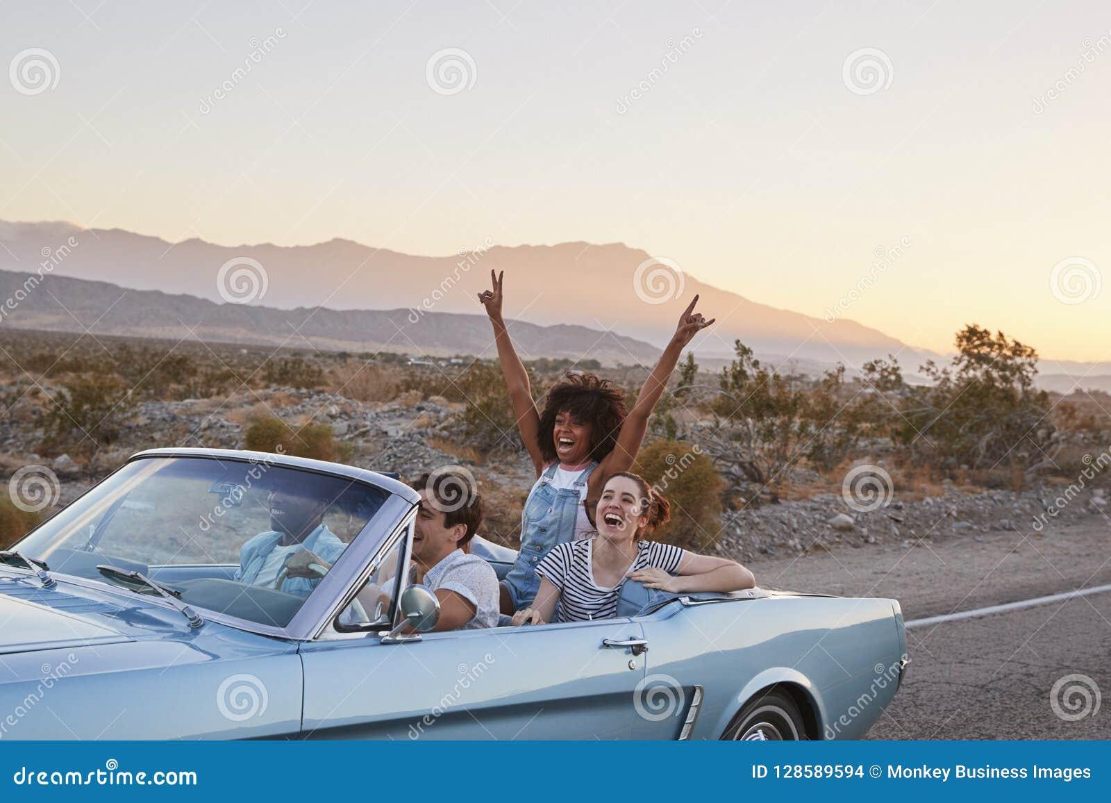 小组驾驶经典敞篷车汽车的旅行的朋友