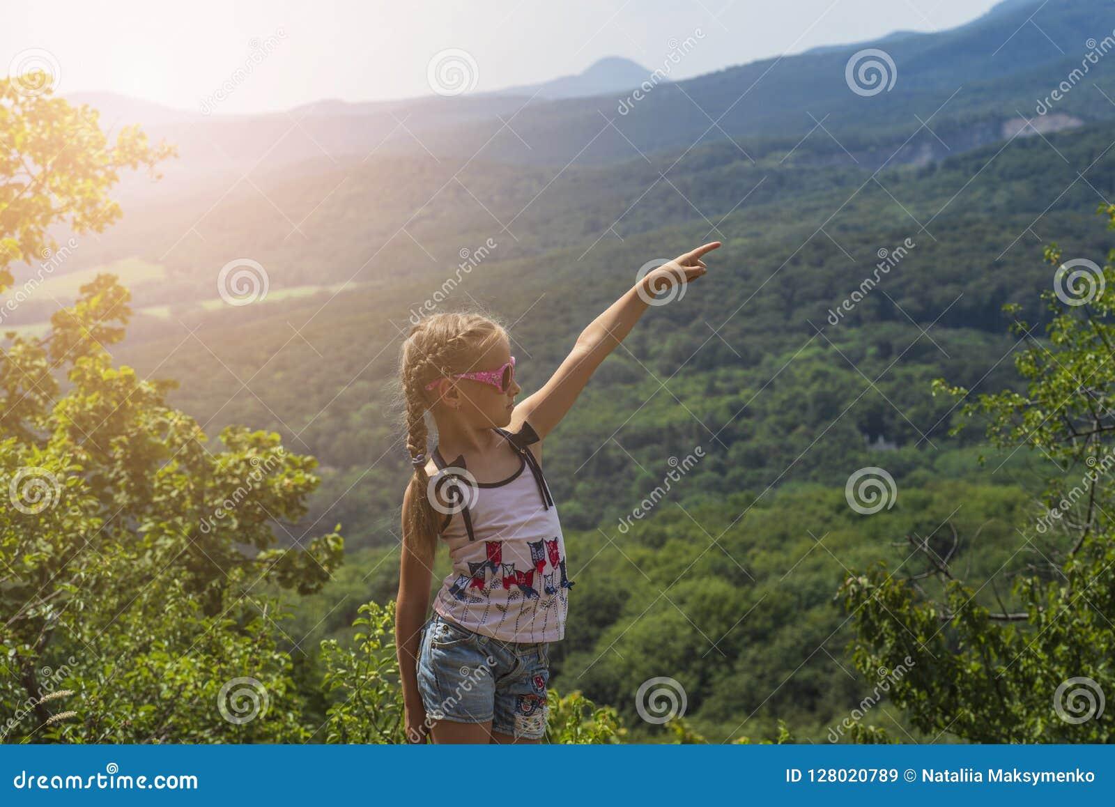 小聪慧的女孩坐在山边缘并且调查在山的距离