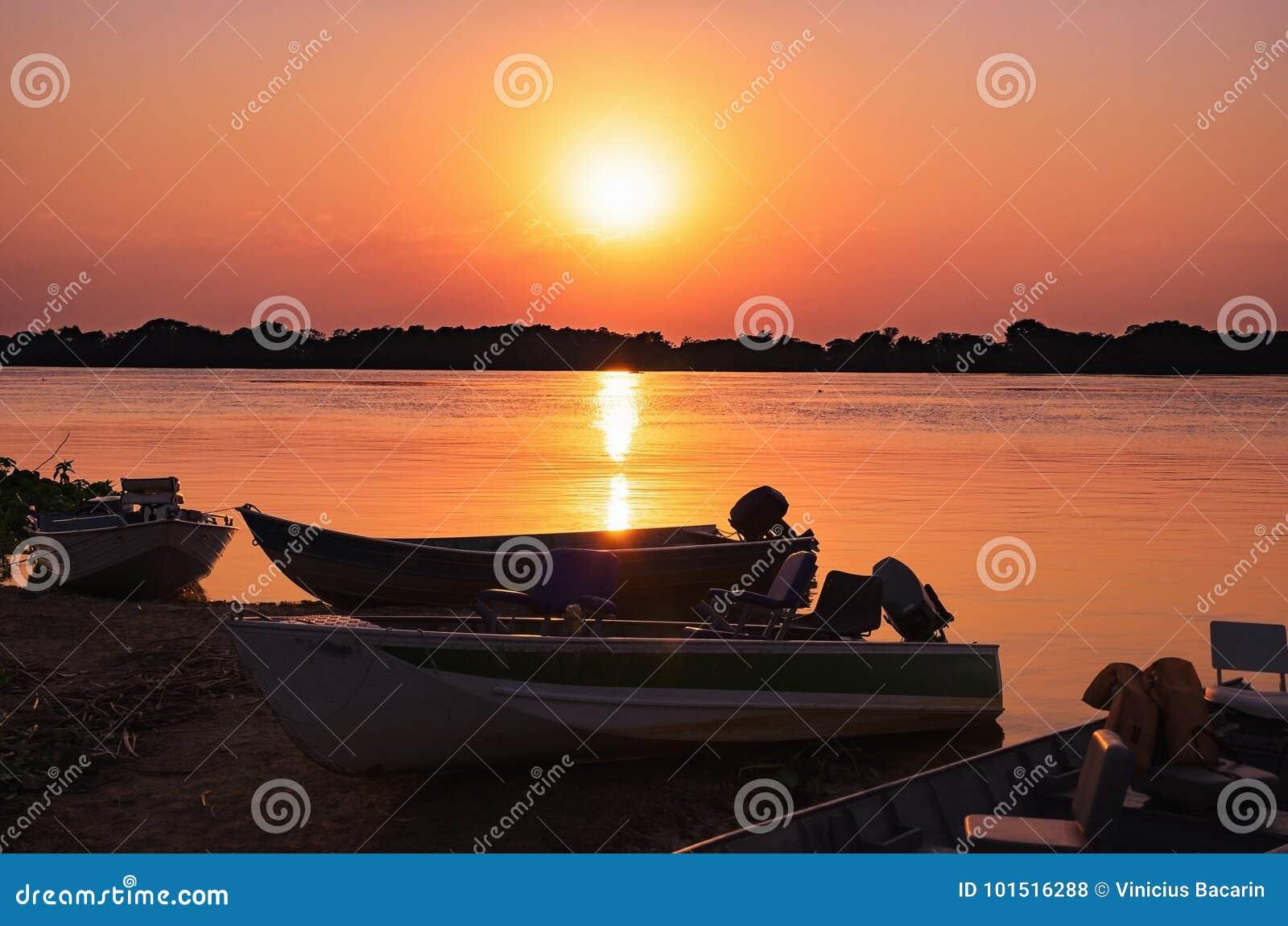 小船剪影的美妙的风景在惊人的日落的