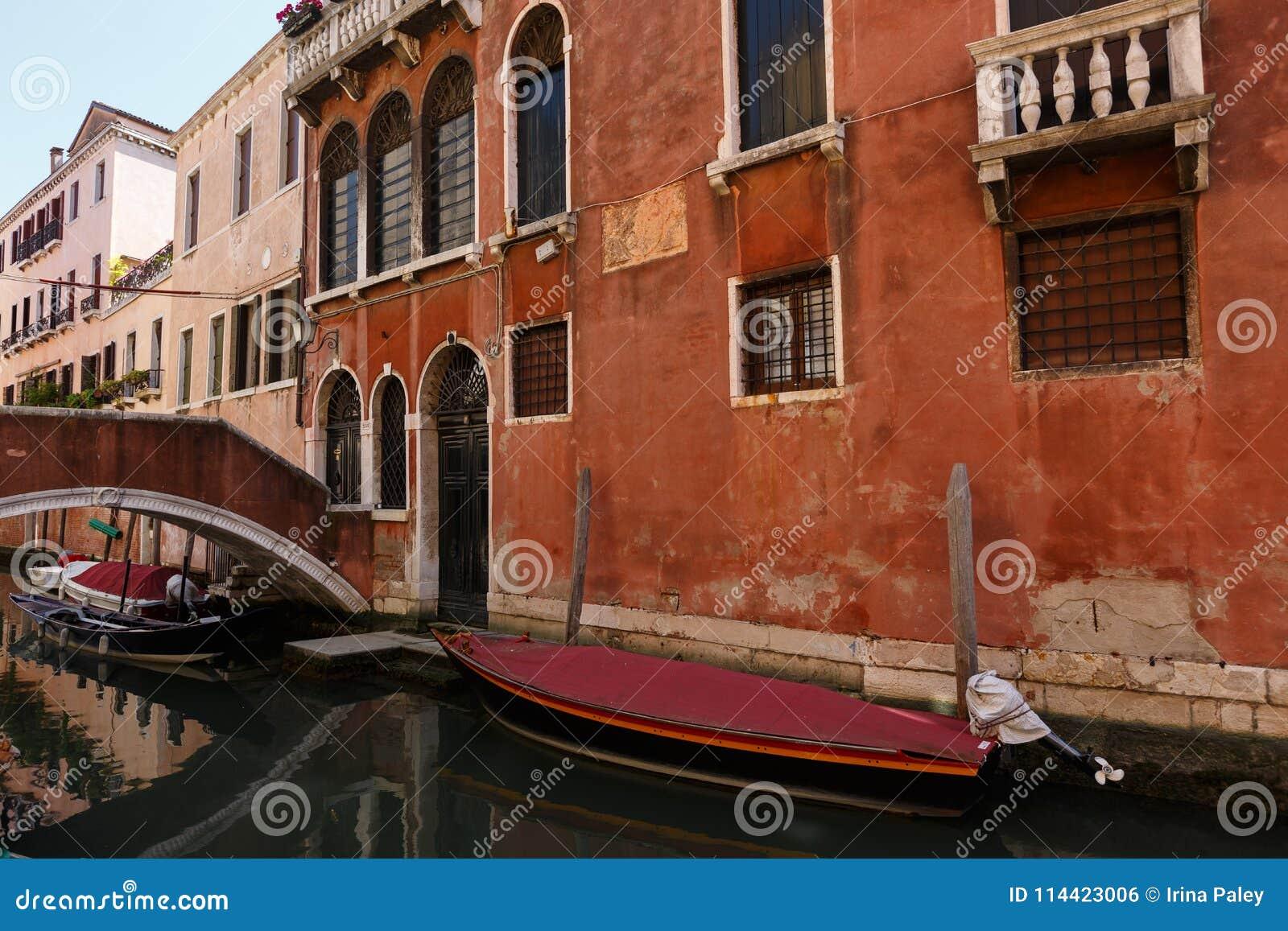 小船和长平底船典型的看法在微小的桥梁下在威尼斯运河