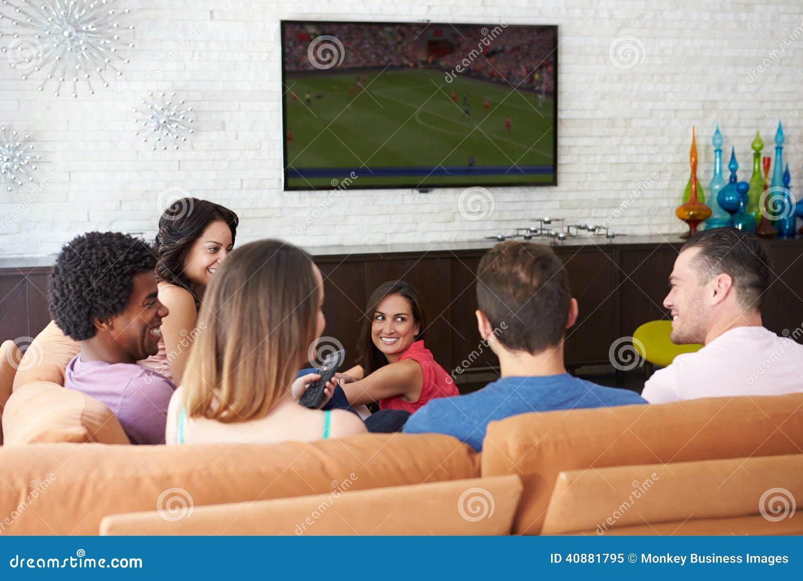 小组朋友一起坐沙发观看的足球