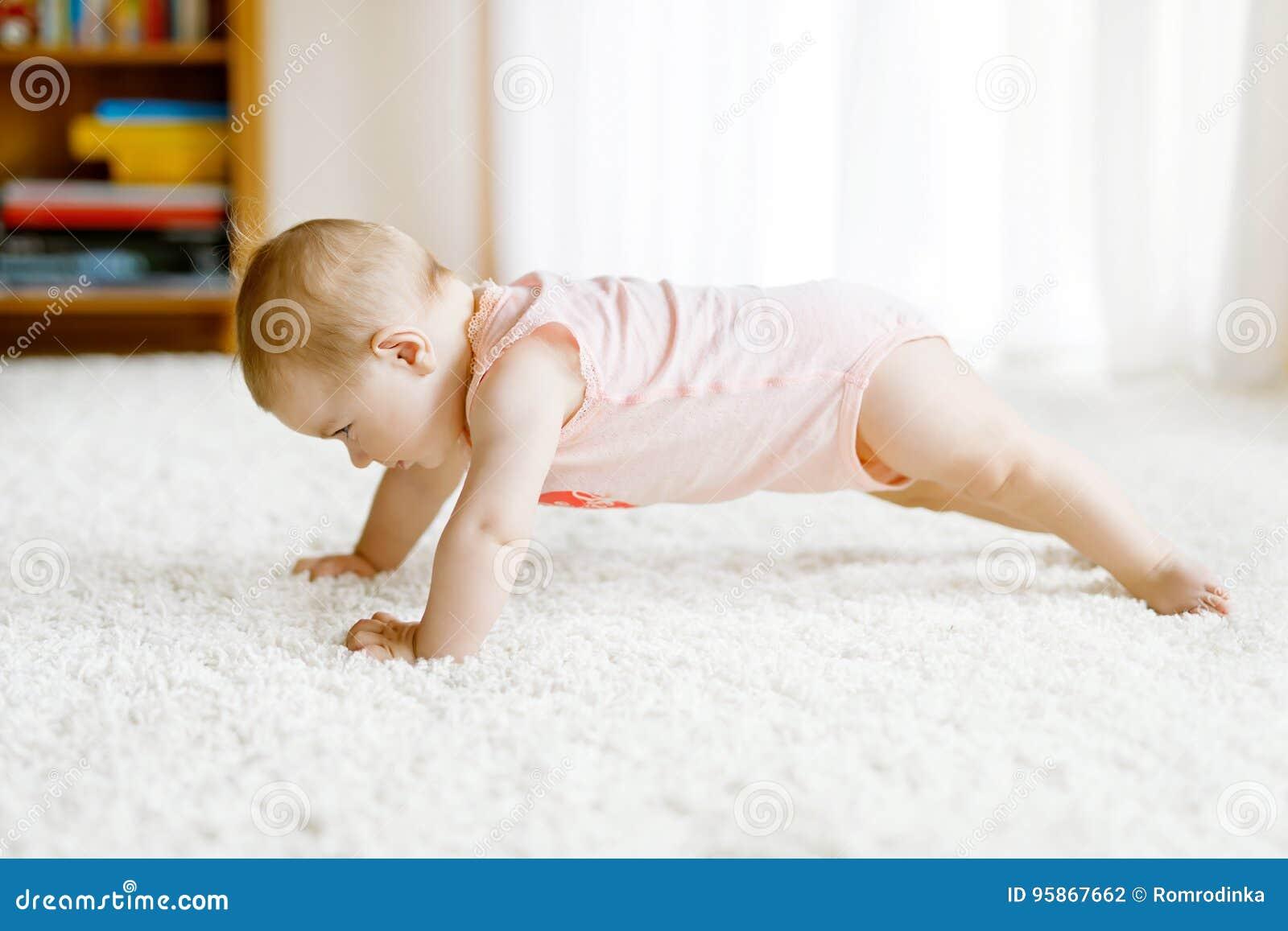 小滑稽的女婴吊环和学会爬行