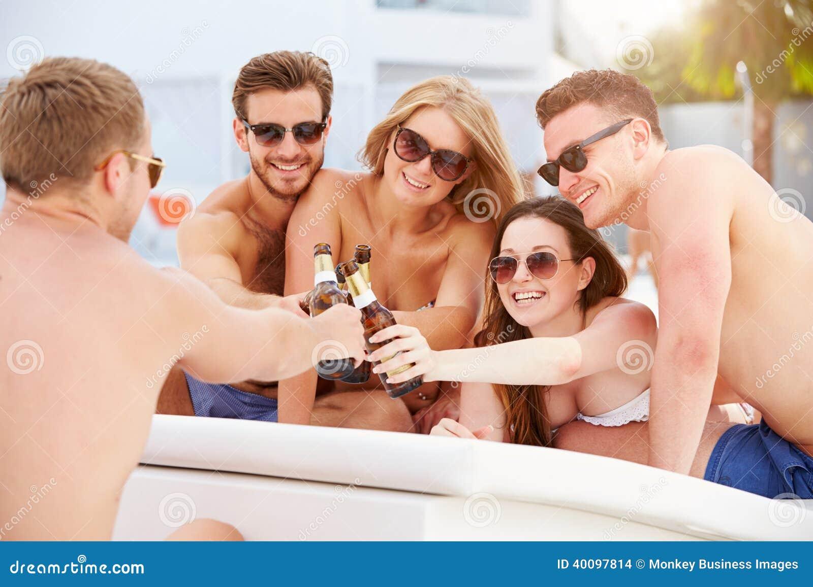 小组青年人在度假放松由游泳池的