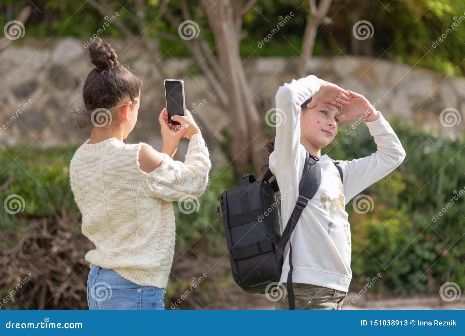 少女拍与室外的智能手机的一张照片