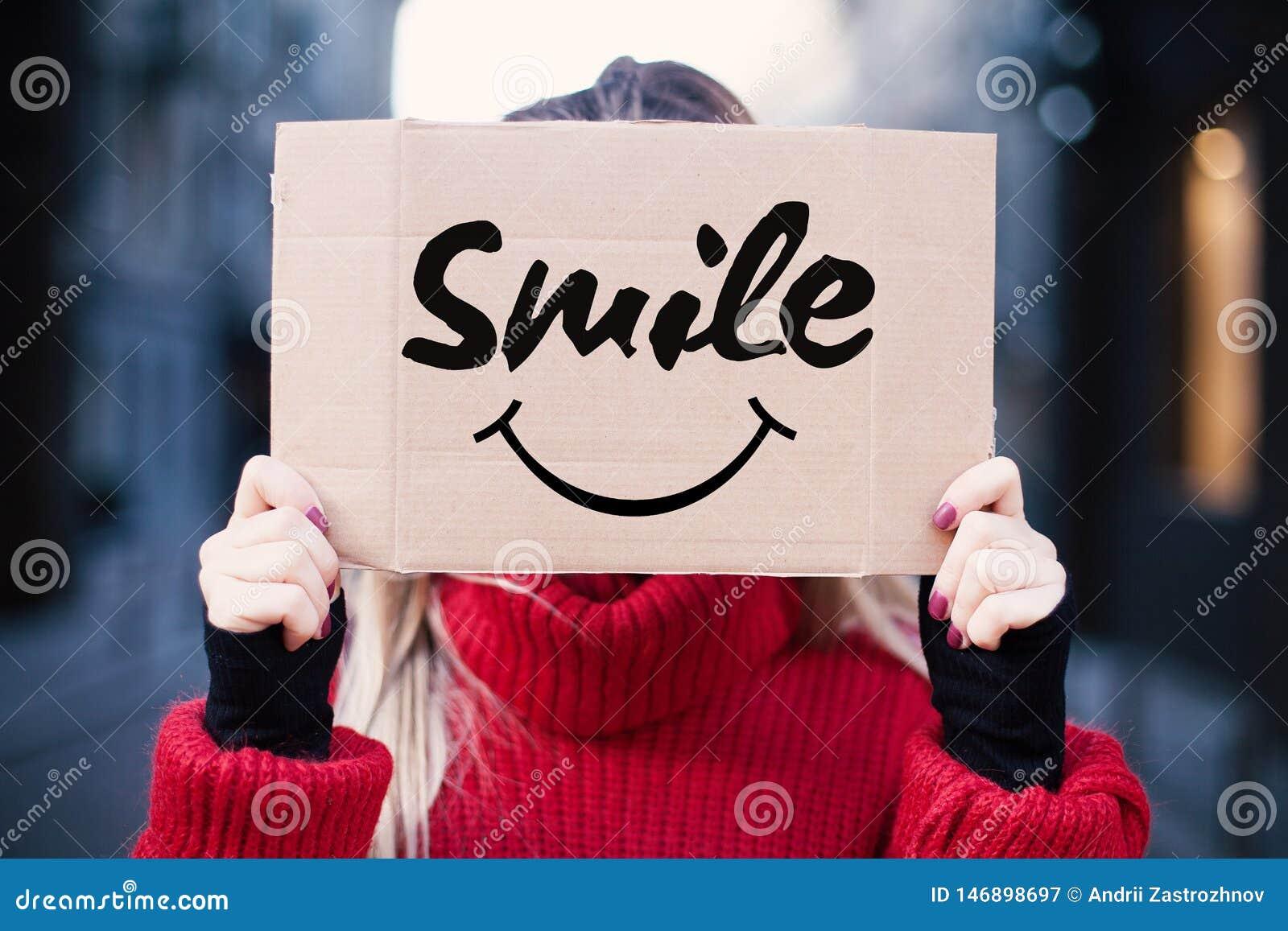 少女拿着与微笑的一个标志 愉快和微笑的概念