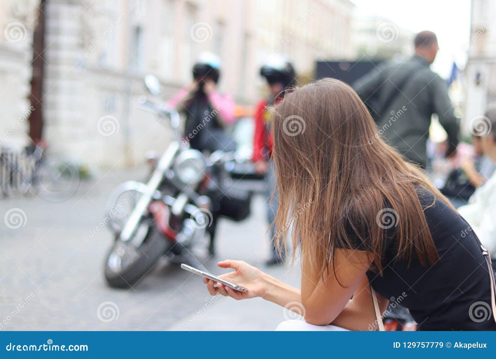 少女调查举行的智能手机 妇女在古城的中心坐一条长凳反对moto