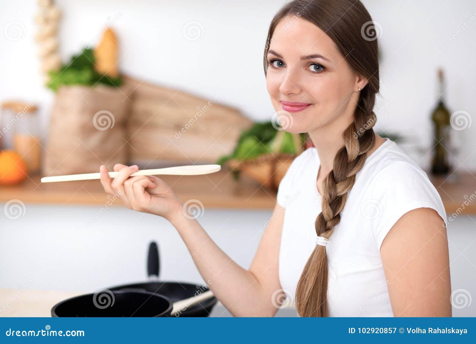 少妇在厨房里烹调 主妇由木匙子品尝汤