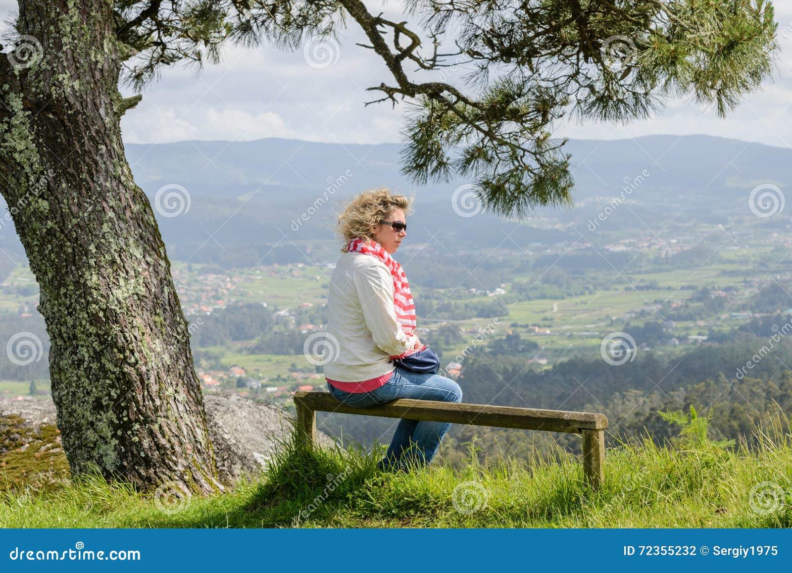 少妇坐看自然的长凳
