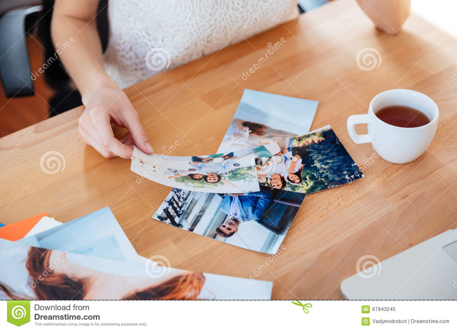 少妇摄影师饮用的茶和选择照片表