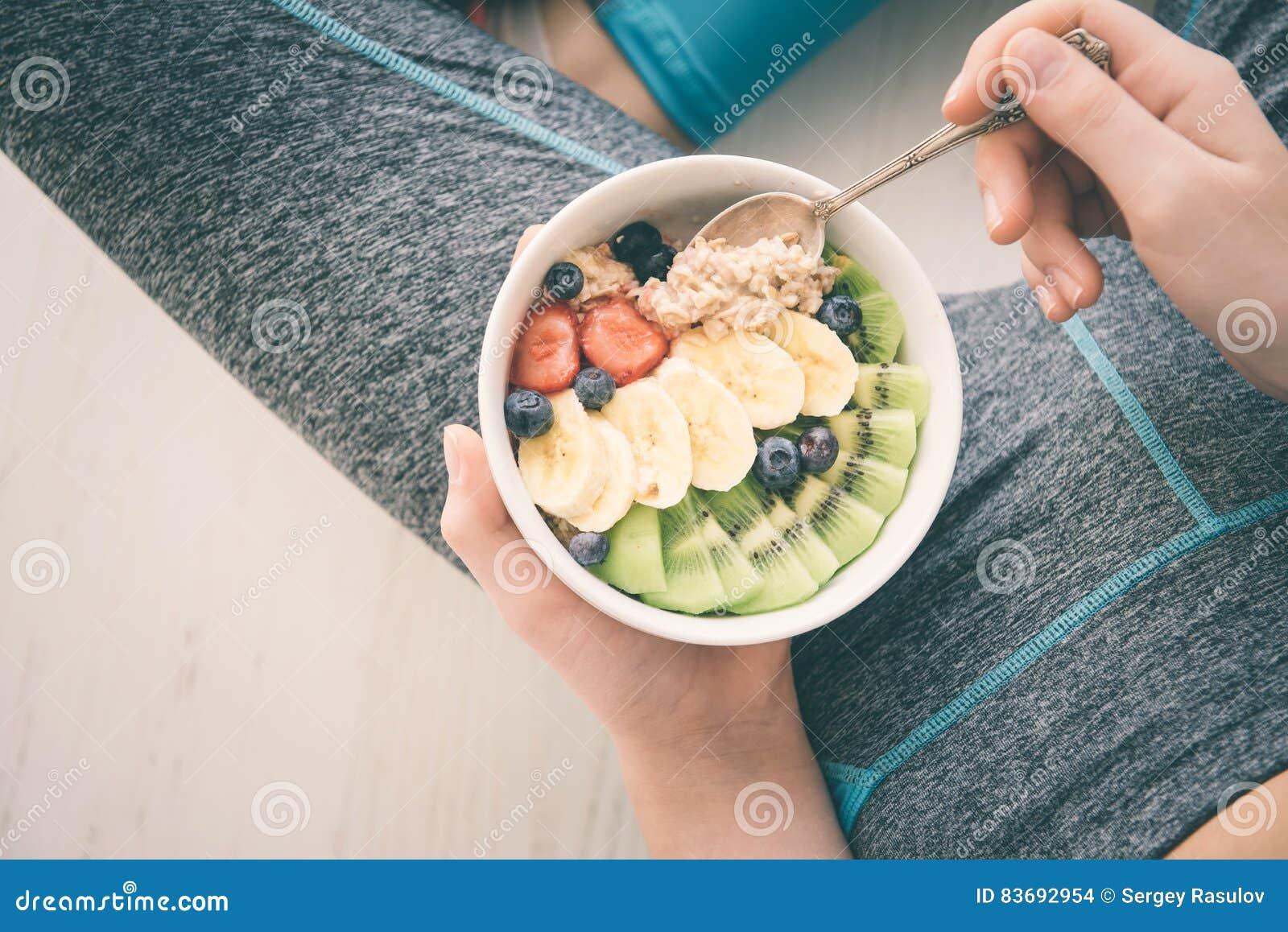 少妇是休息和吃一个健康燕麦粥在锻炼以后