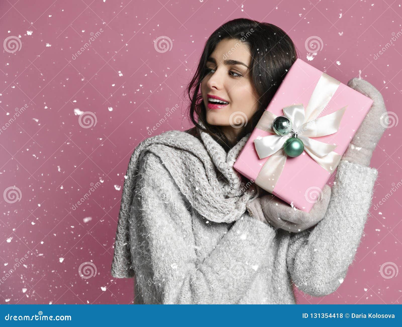少妇画象举行礼物 桃红色背景的微笑的愉快的女孩