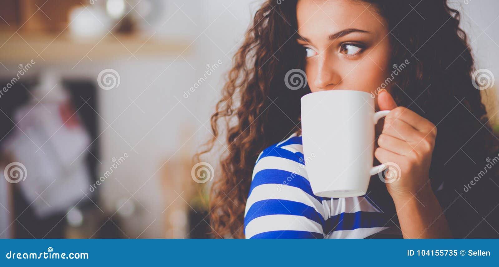 少妇画象有杯子的反对厨房内部背景