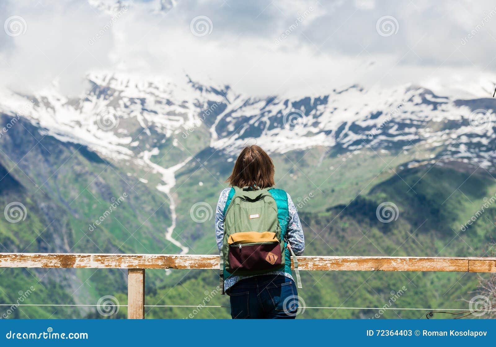 少妇站立在观点并且看起来美好的山风景 远足有背包的女性游人