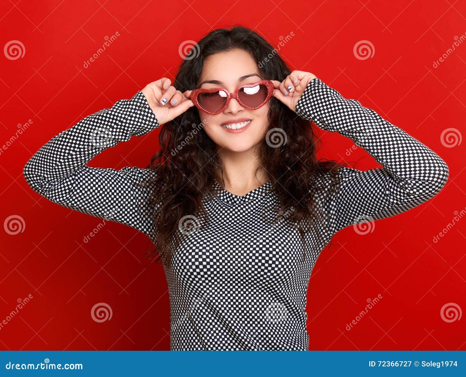少妇美丽的画象,摆在红色背景,长的卷发,太阳镜在心脏塑造,魅力概念