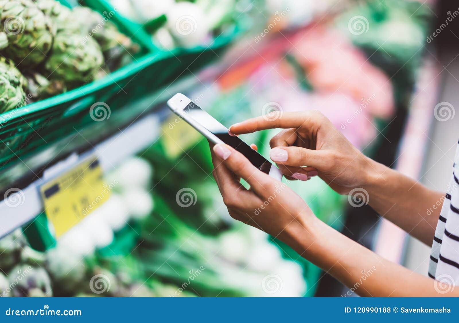 少妇购物购买健康食物在超级市场迷离背景中 使用在sto的智能手机关闭看法女孩购买产品