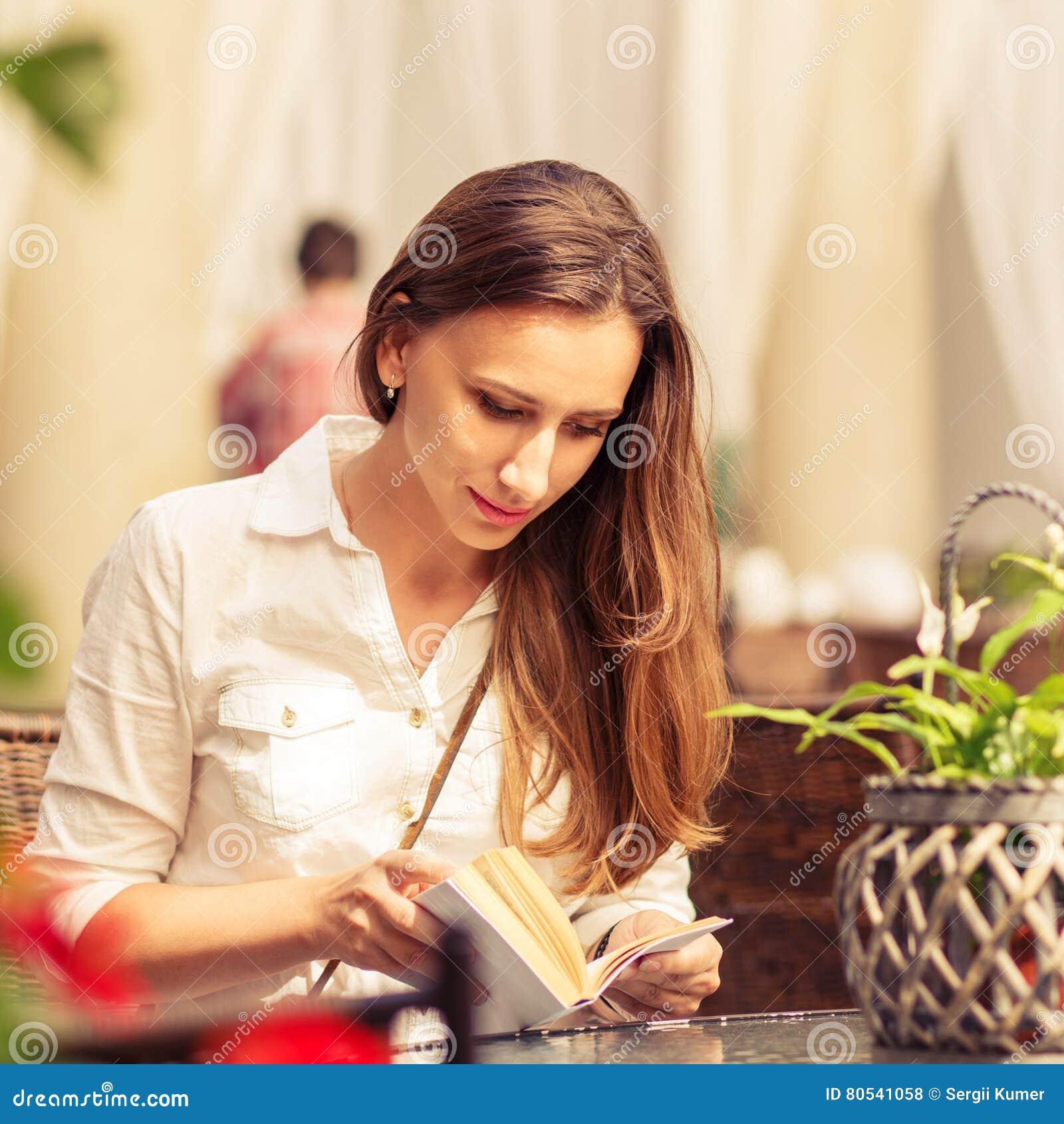 少妇阅读书在咖啡馆的桌上