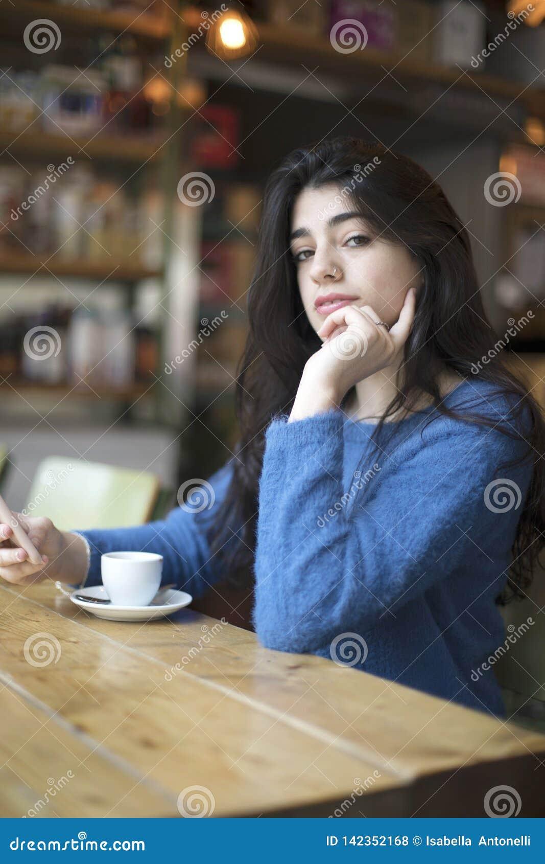 少妇饮用的咖啡和在都市咖啡馆使用她智能手机坐室内 咖啡馆城市生活方式 偶然画象美丽