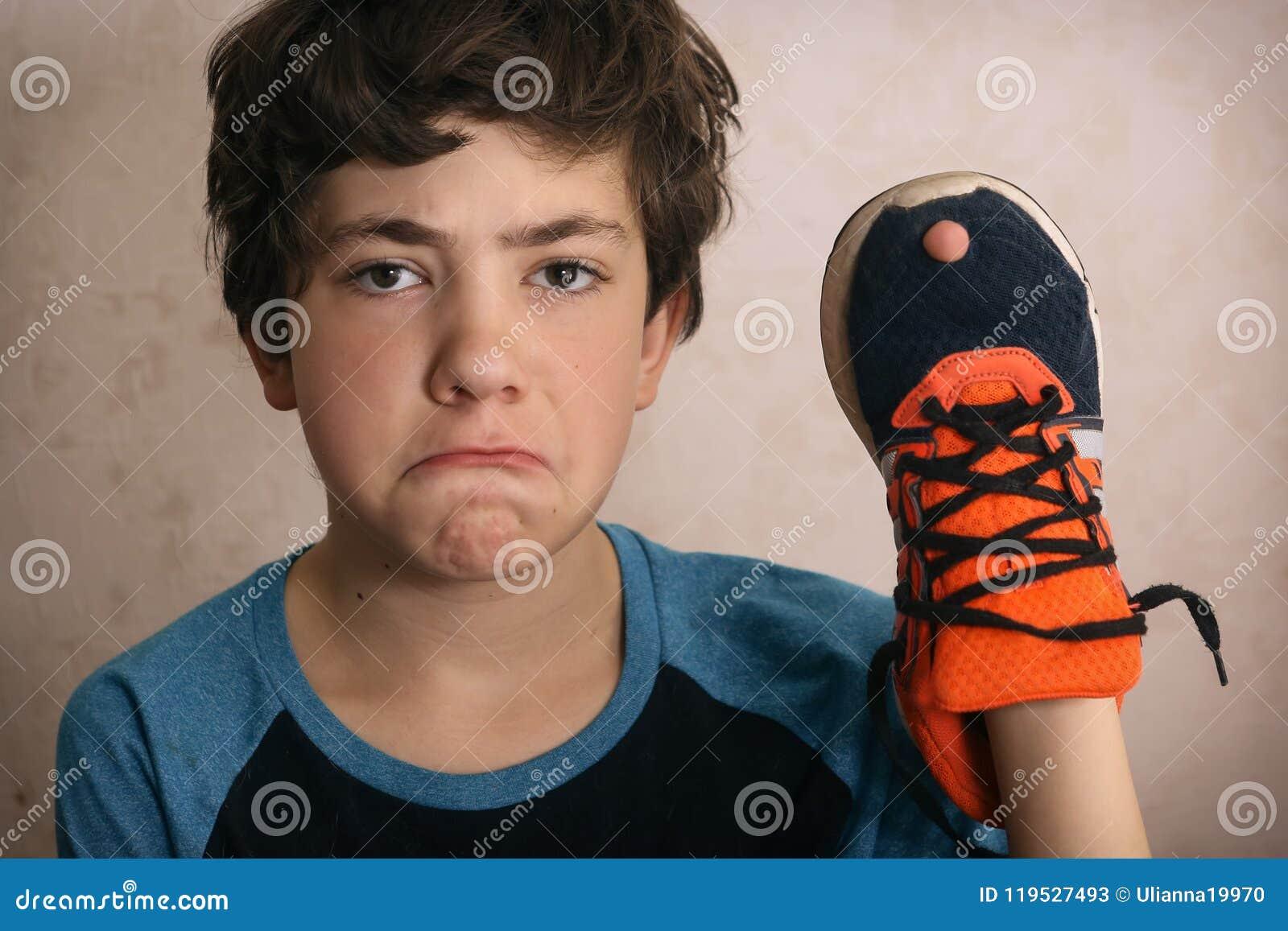少年男孩被挫败关于在他喜爱的教练员鞋子的孔