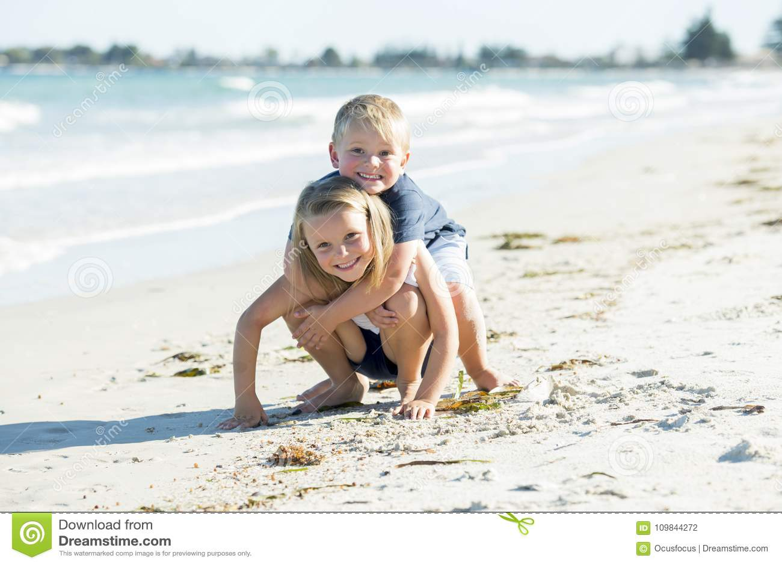少许一起使用在与拥抱他美丽的白肤金发的年轻姐妹enjo的小兄弟的沙子海滩的可爱和甜兄弟姐妹