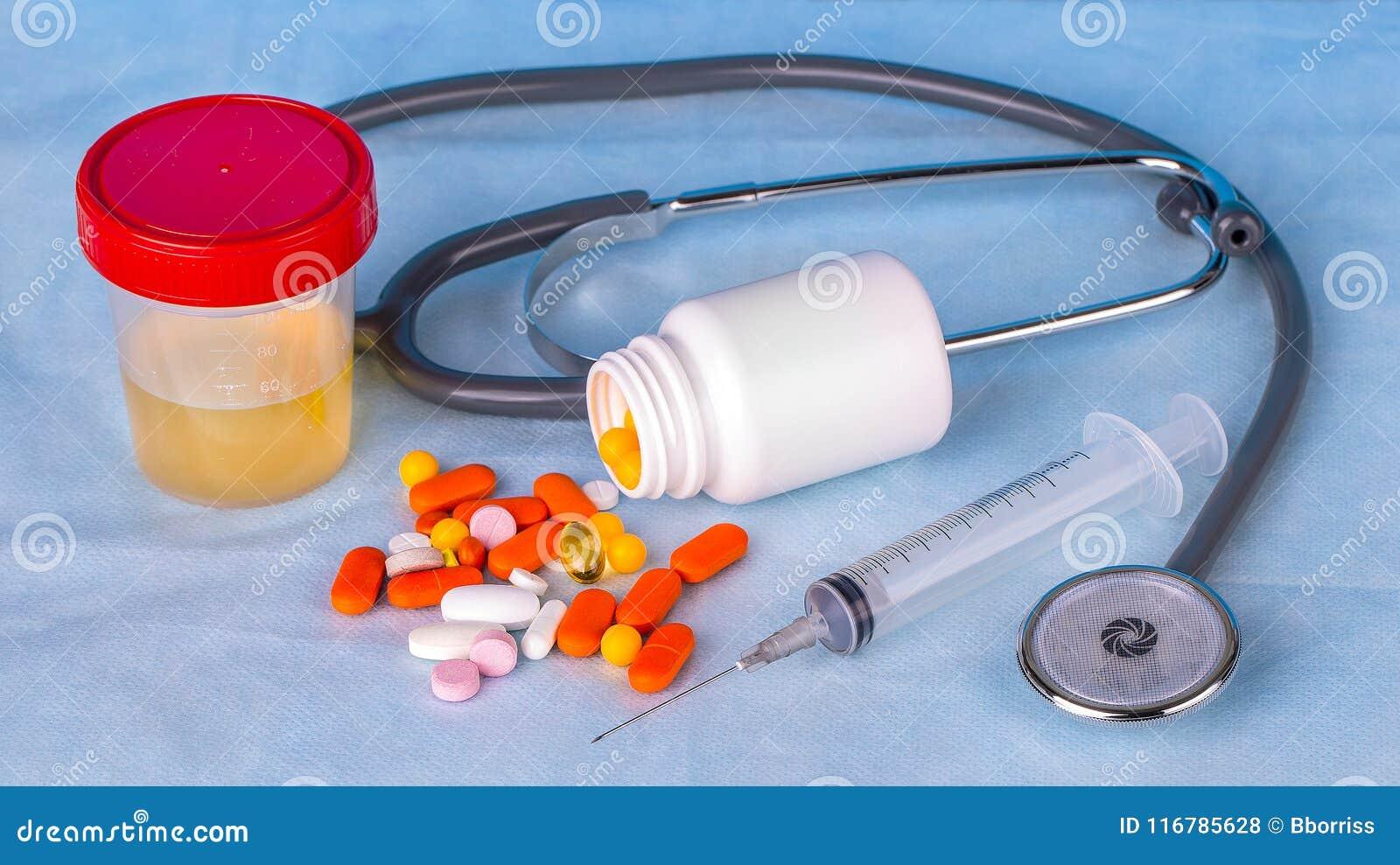 尿容器、注射器、phonedoscope和色的药片在蓝色