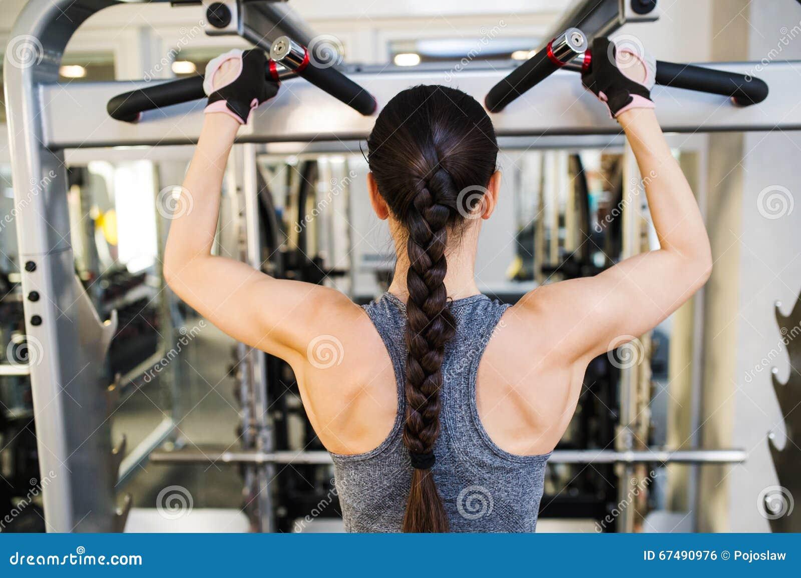屈曲在缆绳机器的健身房的妇女背部肌肉