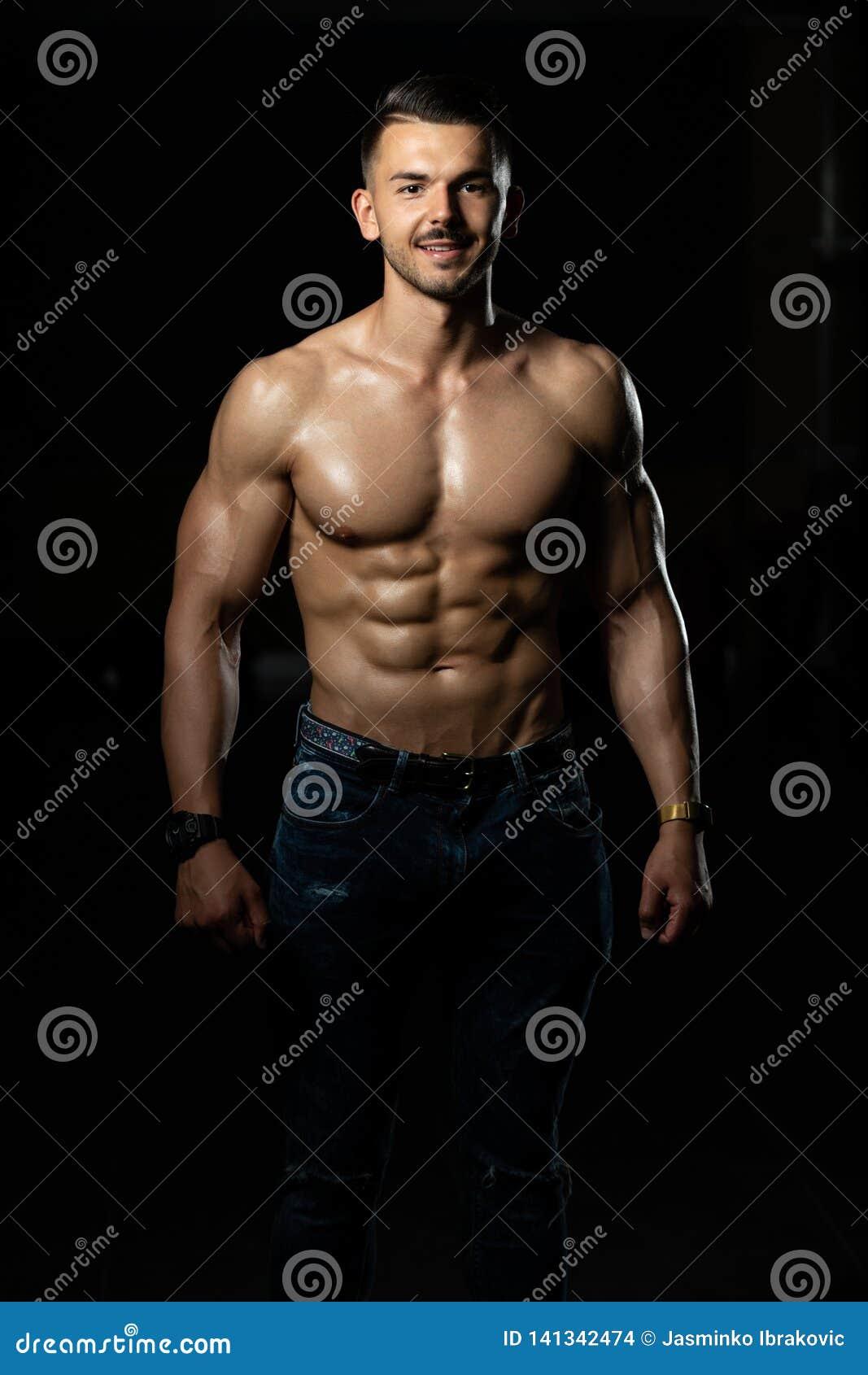 屈曲肌肉的牛仔裤的年轻爱好健美者
