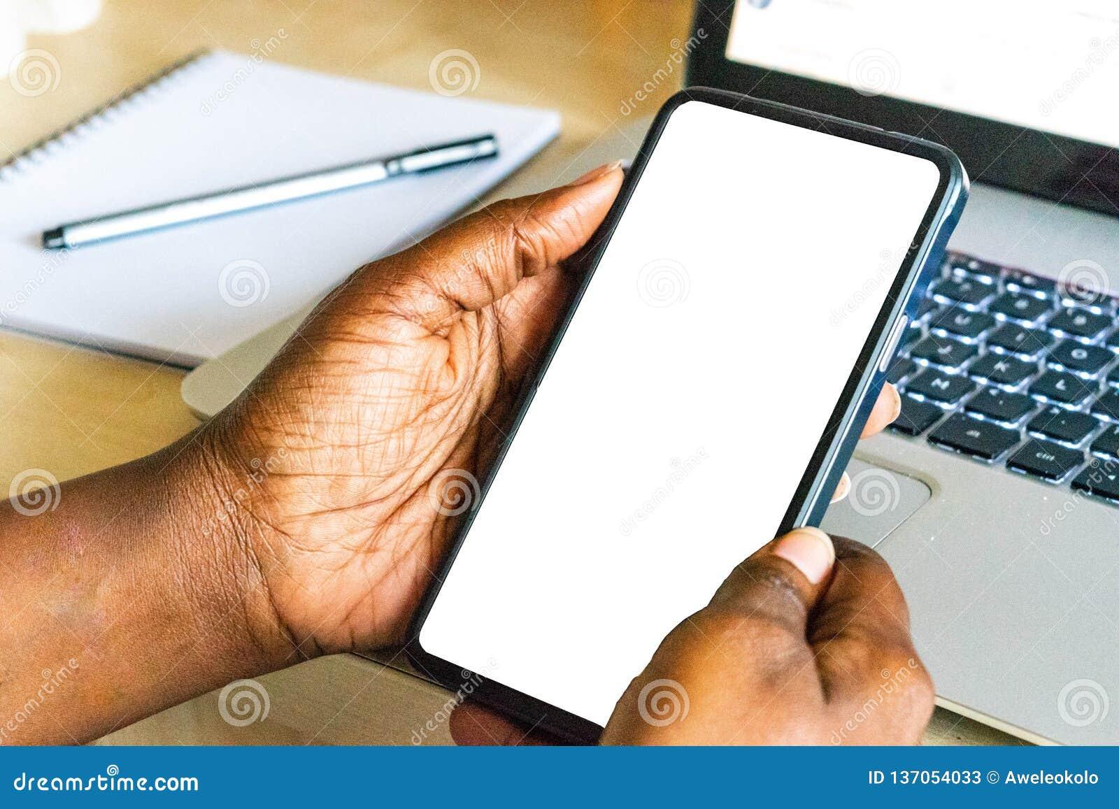 屏幕手机,在非洲妇女的手上 在绿色室外背景的黑女性举行的智能手机与空白的拷贝s