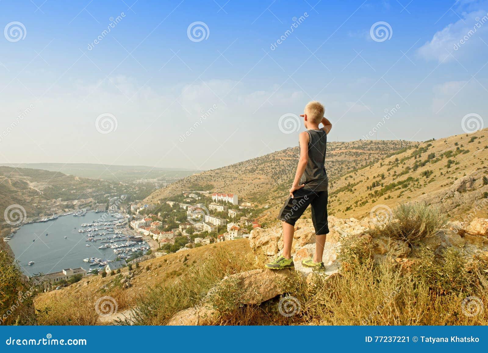 山上面的少年 与游艇和小船的海湾 旅行