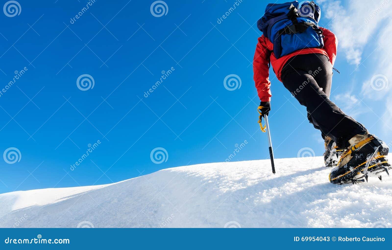 登山人到达一座多雪的山的上面 概念:勇气,成功,坚持不懈,努力,自我实现