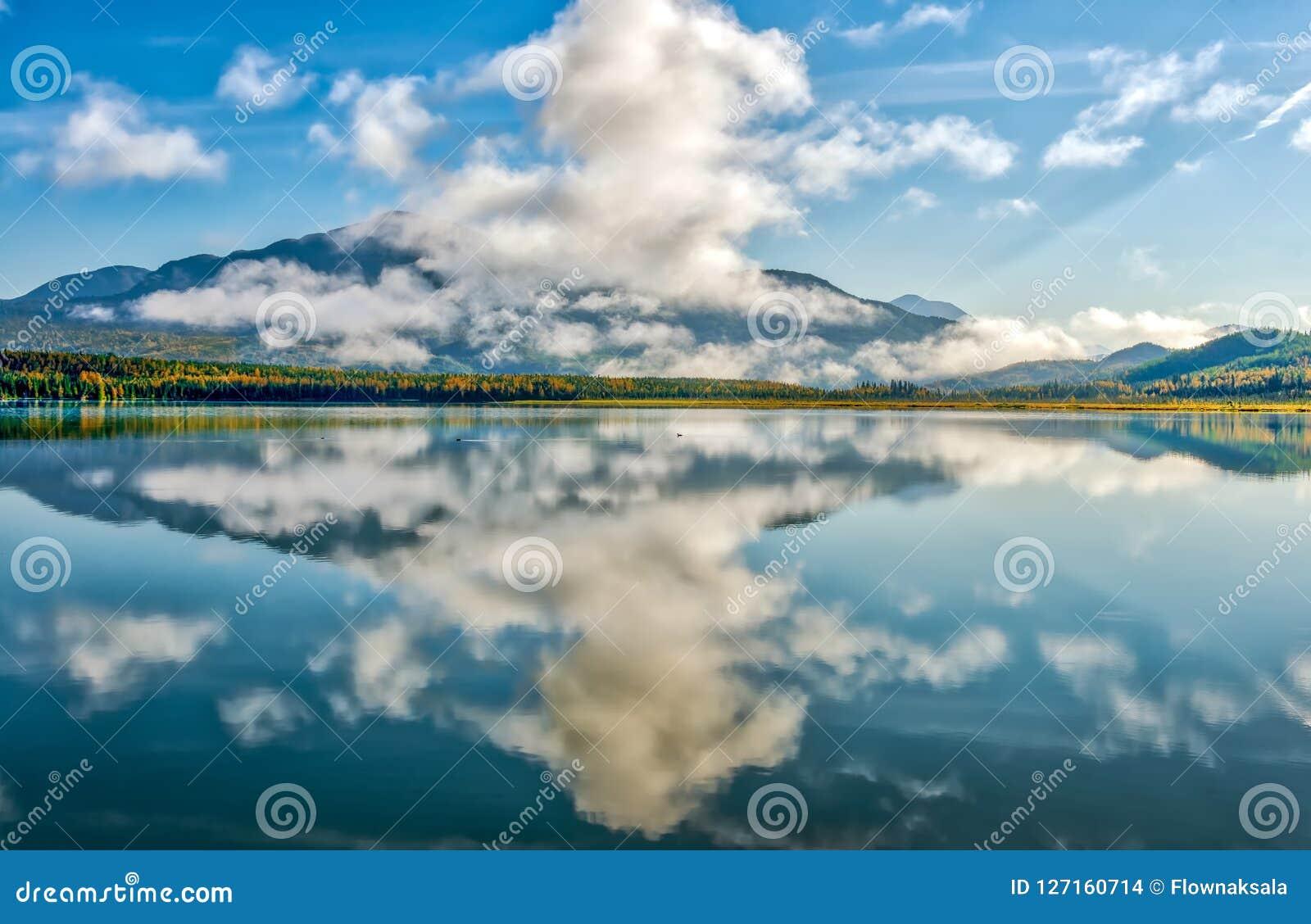 山反射在阿拉斯加的一个生动的蓝色冰河湖