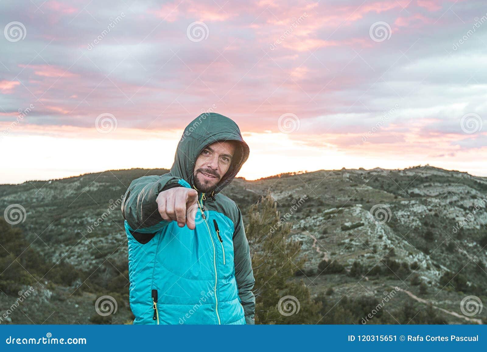 山的人指向照相机的 做一个正面姿态的登山家