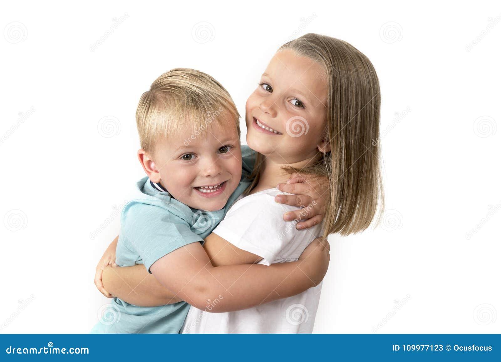 7岁摆在与她小的3岁的可爱的白肤金发的愉快的女孩在白色背景隔绝的兄弟微笑的快乐
