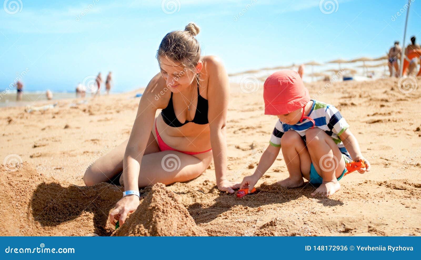 3岁照片小孩男孩大厦与年轻母亲的沙子城堡海洋海滩 获得的家庭放松和乐趣