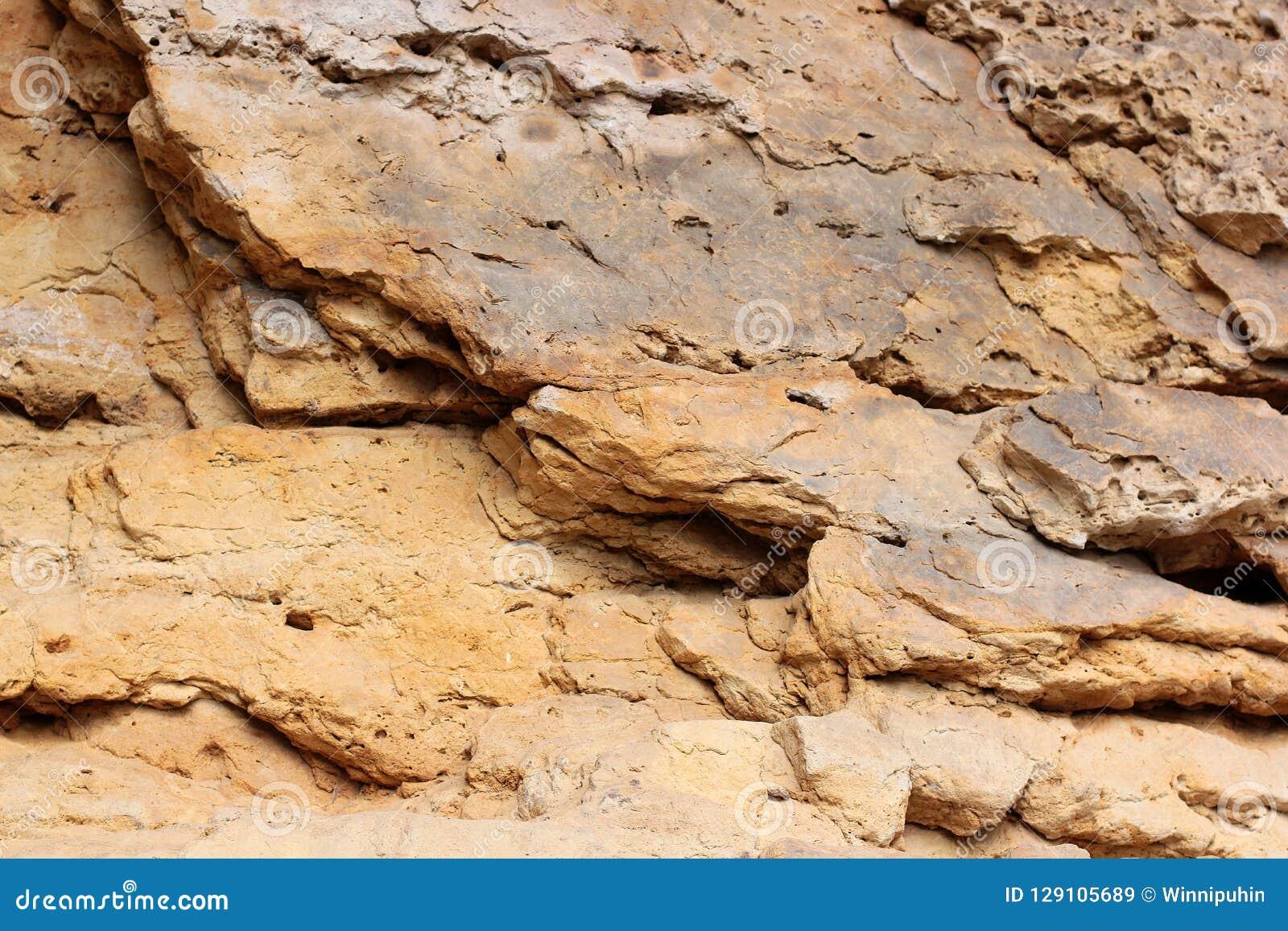 岩石分层堆积-岩石的五颜六色的形成被堆积在上百年 与引人入胜的纹理的有趣的背景