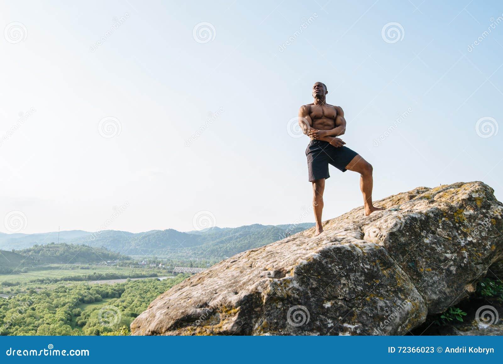 岩石的英俊的黑人非裔美国人的运动员人在山 人体的秀丽和完美