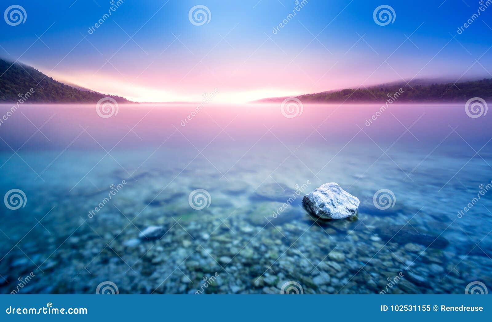 岩石长的曝光在Pebble海滩的湖有紫色日出光的