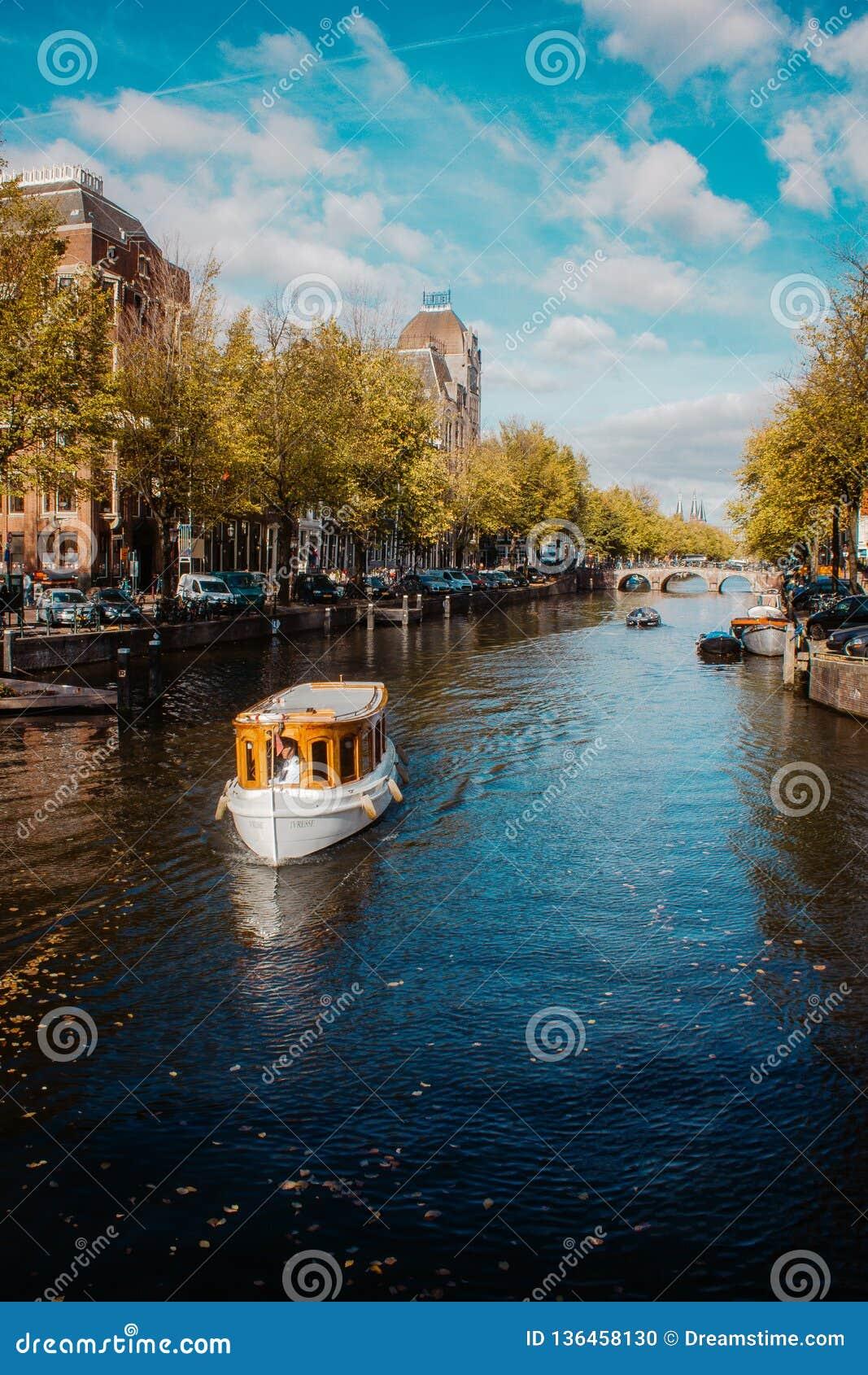巡航在其中一条的游览小船著名阿姆斯特丹运河在美好,晴朗的秋天天