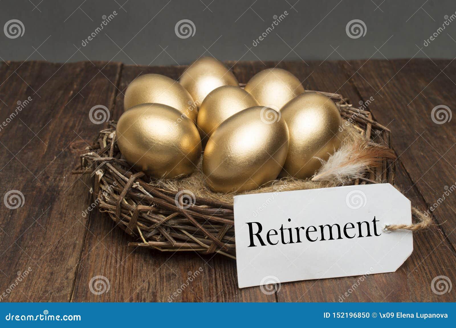 巢用与标记的金黄鸡蛋和在木背景的词退休 成功的退休的概念