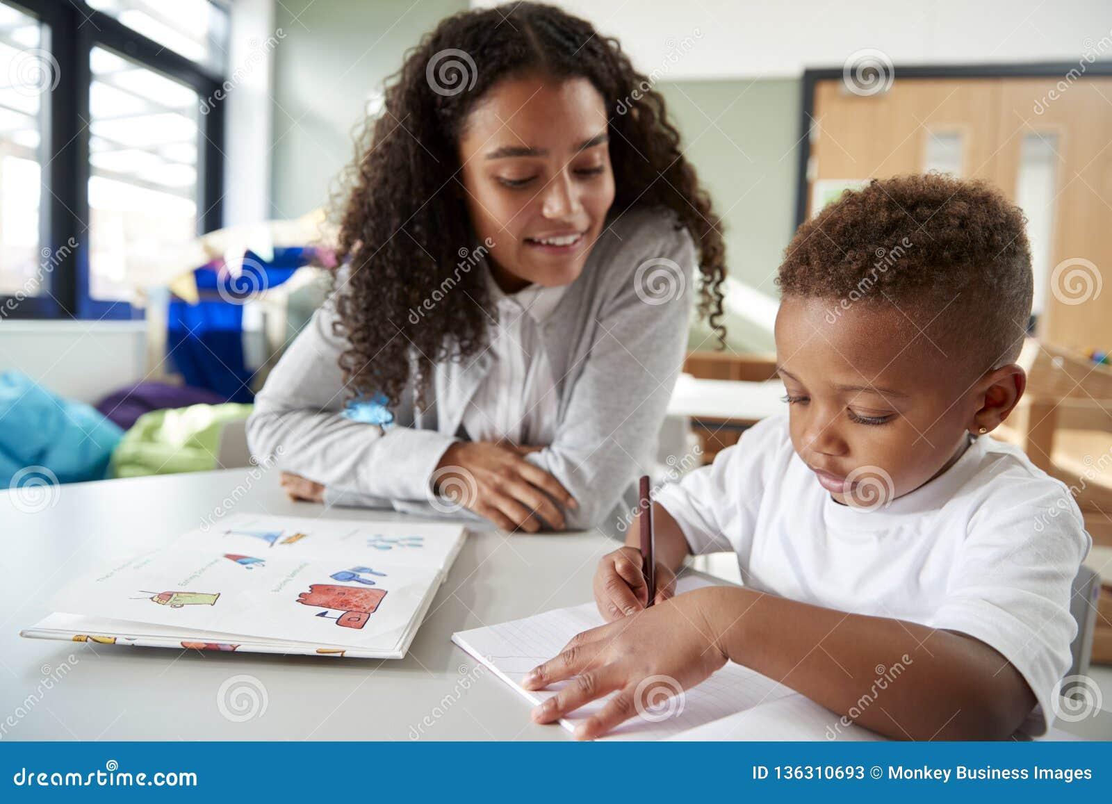 工作一在一个的女性婴儿学校老师与一位年轻男小学生,坐在桌上写在教室,正面图,克洛